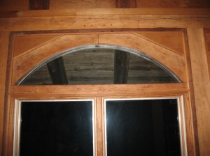 This shows the diagonal bracing on the front wall which frames the fan lite.  The braces and cross member at the bottom are all joined to the posts and the beam by pegged mortises and tenons.  They are joined to each other by a pegged loose tenon.