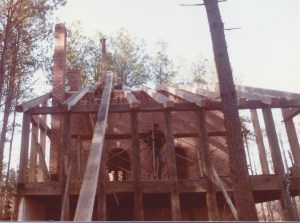 Rafter raising day.  The tall pole sticking up above the brick wall is the gin pole.  There's a pulley on top: a rope went over the pulley and to a tractor on the other side to pull the rafters up.
