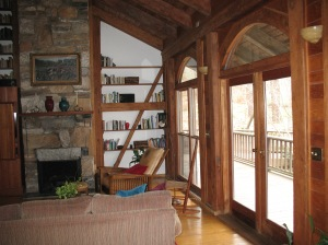 "This view of the living room shows the stone fireplace by James ""Fuzzy"" Monnes, with a heart pine mantel by Bill Wallace.  The diagonal brace is connected to the post by a pegged mortise and tenon, to the horizontal beam by a half lap, and to the floor joist by a pegged half lap."